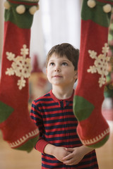 Caucasian boy looking at Christmas stockings