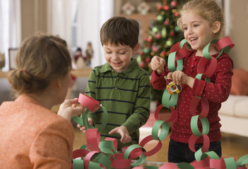 Mother and children making Christmas paper chains