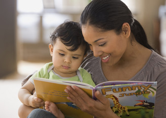Mixed race mother reading book to baby boy