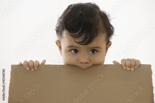 Mixed race baby boy holding piece of cardboard