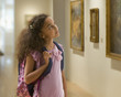 Mixed race girl looking at painting in museum