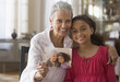 Grandmother and granddaughter holding photograph