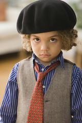 Serious mixed race boy wearing cap