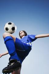 Caucasian woman kneeing soccer ball