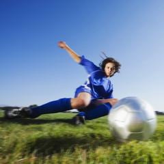 Caucasian woman kicking soccer ball