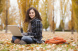 Caucasian woman using laptop in autumn leaves
