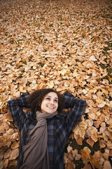 Caucasian woman laying in autumn leaves