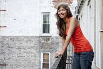 Mixed race woman leaning on fire escape railing
