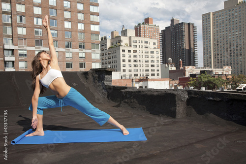 Mixed race woman practicing yoga on rooftop