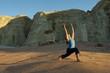 Caucasian woman practicing yoga in desert