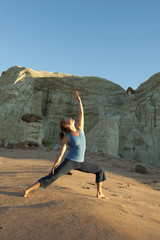 Caucasian woman practicing yoga in desert