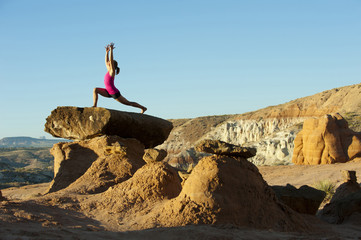Caucasian woman practicing yoga on top of rock formation