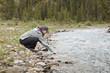 Caucasian woman reaching into stream