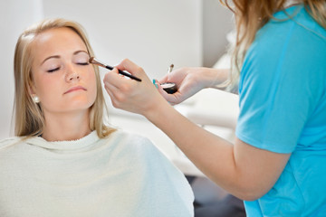 Beautician Applying Make Up To Woman