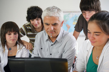 Teacher and pupils gathered around computer