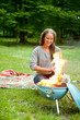 Female Preparing Meal On Flaming Barbecue