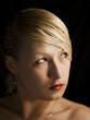 Retrato mujer rubia mirando a un lado en el fondo negro