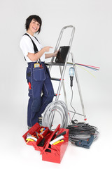 Female electrician pointing to laptop