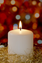 Cream candle with gold tinsel and blurred light background