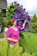 Seniorin mit Kletterpflanze Clematis