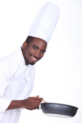 A chef holding a frying pan