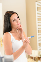 Woman expecting pregnancy test result in bathroom