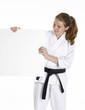 Niña en artes marciales sujetando un panel blanco.