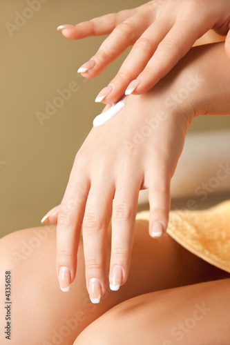 woman applying skin creme to hands