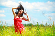 Happy beautiful woman dancing in meadow