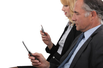Business partner both checking e-mails on cellphone