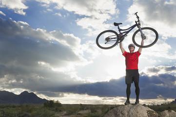 Caucasian man lifting mountain bike in remote area