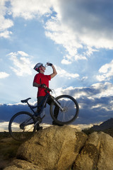 Caucasian man with mountain bike drinking water