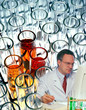 Scientist working in laboratory with test tube design behind him