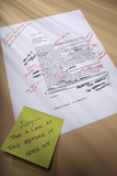 Stick note on paperwork covered with revisions