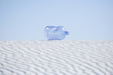 Empty water jug laying on desert sand dune