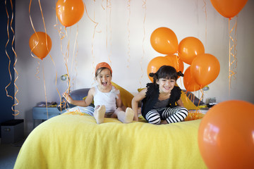 Girls sitting on bed together with balloons