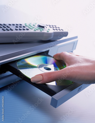 woman putting DVD into DVD player