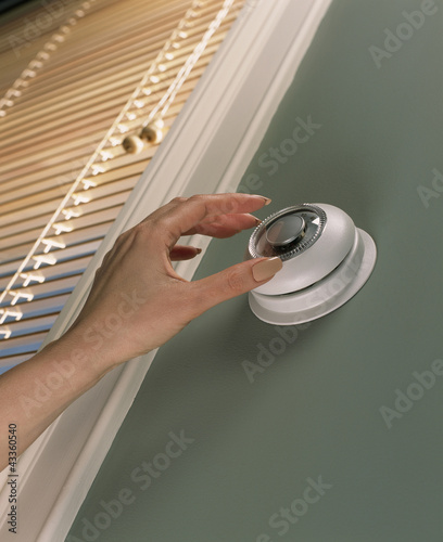 Woman changing temperature on thermostat
