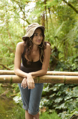 Hispanic woman leaning on railing in forest