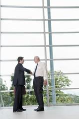 Hispanic businessmen shaking hands in lobby