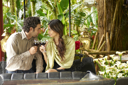 Hispanic couple sitting in carriage drinking red wine