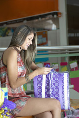 Hispanic woman holding gift and using cell phone