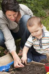 Hispanic mother gardening with son