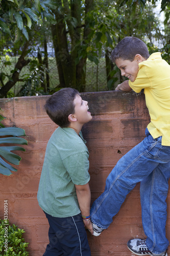 Hispanic boy helping friend climb wall