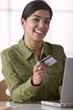 Hispanic woman shopping online with credit card