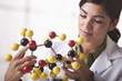 Hispanic scientist looking at molecule model