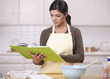 Hispanic woman reading recipe in kitchen