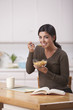 Hispanic woman eating cereal for breakfast