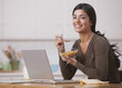 Hispanic woman eating cereal for breakfast and looking at laptop