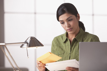 Hispanic woman looking at mail